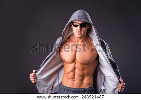 Handsome, muscular man in sportswear posing on a dark background. Confident man in an unbuttoned jacket. Bodybuilder man in sunglasses and a sports jacket. - stock photo