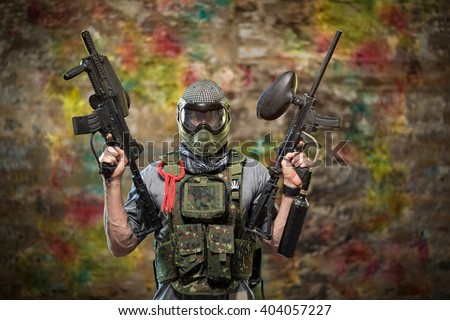 Handsome paintball gamer with guns in camouflage uniform  - stock photo