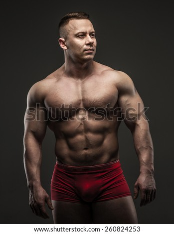 Handsome power athletic guy posing in studio. Isolated on grey - stock photo