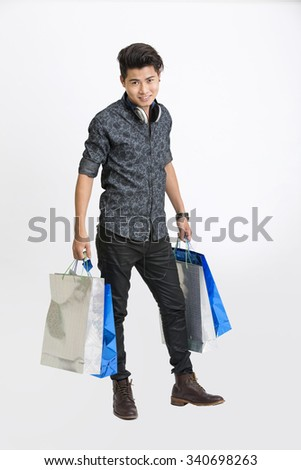 Handsome young man standing with shopping bags with head phone on white background. - stock photo