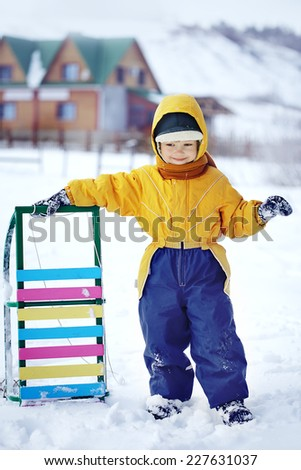 happy boy with sled outdoors - stock photo