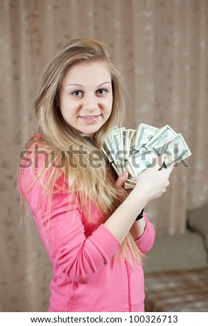 happy casual girl with bundles of US dollars  in home interior - stock photo