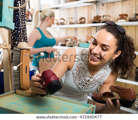 happy cheerful girl showing a chosen pair of shoes while her friend still choosing - stock photo