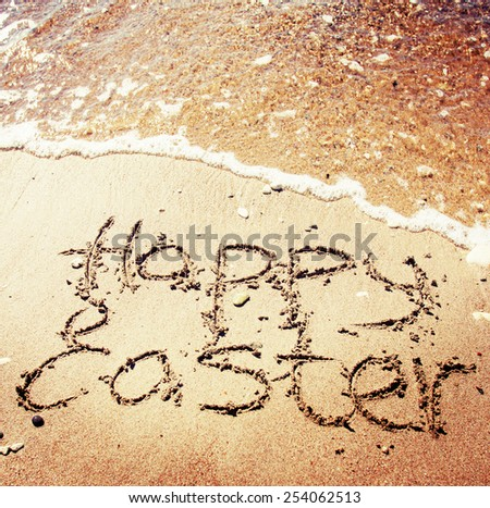 """""""Happy easter"""" written in the sand on sea background - stock photo"""