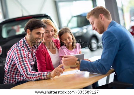 Happy family in car dealership choosing their new car, friendly car agent helping  - stock photo