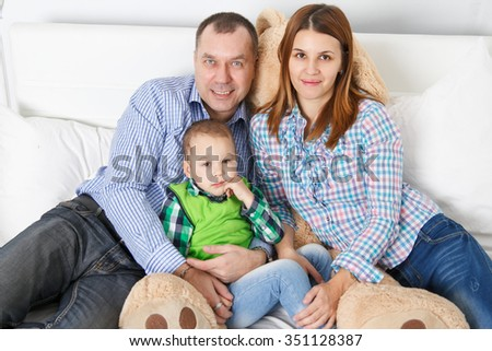 happy family on bed. Mother, father and their little son lying on white sheet. They embrace each other and smile. - stock photo