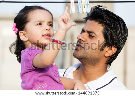 happy father and dauther in the outdoors, Indian man with his two year old daughter - stock photo