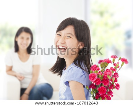 happy girl looking back and hiding a bouquet of carnations - stock photo
