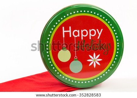 """""""Happy Holidays"""" sign on red and green cannister used for presenting gifts. - stock photo"""
