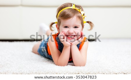 Happy little girl lying on the floor at home - stock photo
