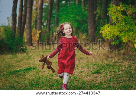 happy little girl running down the wood path with her teddybear  - stock photo