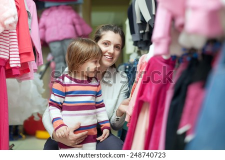 Happy mother and daughter chooses wear at clothes shop. Focus on girl - stock photo