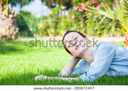 Happy relaxed woman lying on the green grass  - stock photo