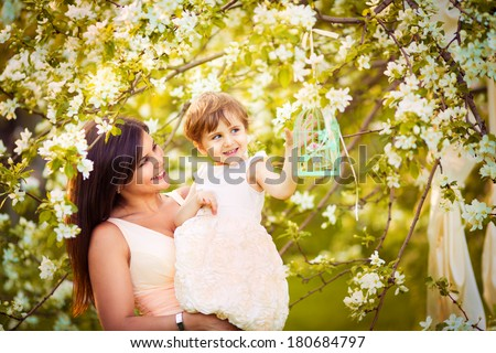 Happy woman and child in the blooming spring garden.Mothers day holiday concept - stock photo