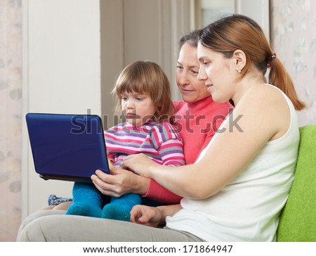 Happy women  of three generations with laptop on sofa  - stock photo