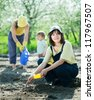 Happy women with child works at garden in spring - stock photo