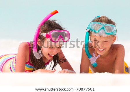 Happy young boy and girl with snorkels on sandy beach, sea in background. - stock photo