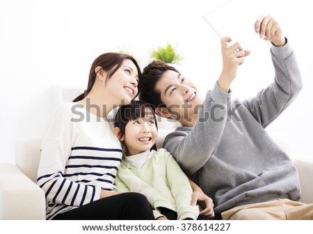 Happy young family taking selfies on sofa - stock photo