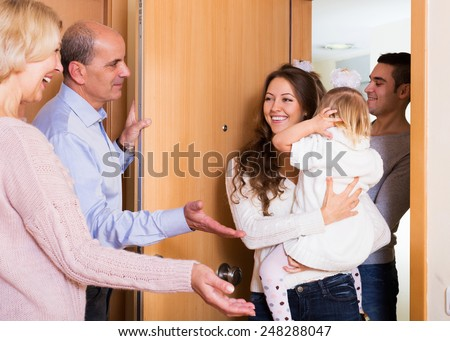 happy young family with two daughters visiting grand parents  - stock photo