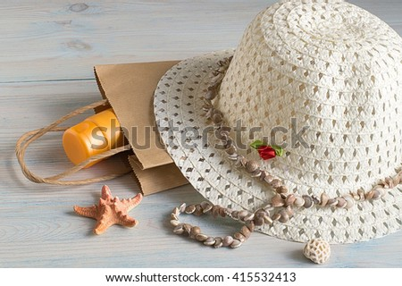 Hat, paper bag and sea shells on a light wooden background. - stock photo