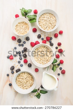 healthy breakfast: oat flakes in bowls, fresh berries and milk on white wooden background, top view - stock photo