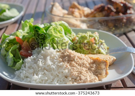 healthy low fat meal with salad rice guacamole  Top view at white plate diet super-food served on wooden table, - stock photo