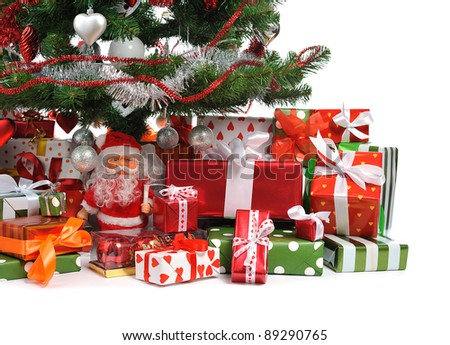 heap of festive gift boxes under decorated Christmas tree - stock photo