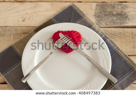 Heart on plate with fork and knife - stock photo
