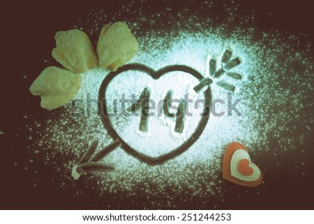 14. Heart with arrow on the flour on the black table. Cookies and red heart. Toned. - stock photo
