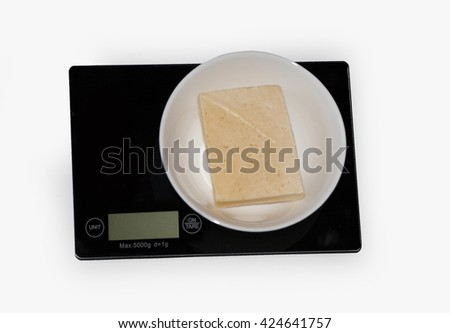 Ð¡heese on a digital white kitchen scale. (weighing products) - stock photo