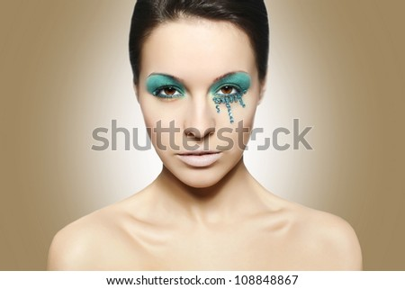 High fashion look.glamour closeup portrait of sexy beautiful brunette woman with black eyes and blue bright colorful makeup caucasian young female with perfect clean skin. Brown background - stock photo