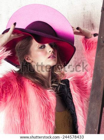 High fashion portrait of young woman in pink hat and fur coat at the white wall with wooden ladder - stock photo