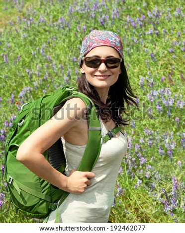 Hiking  woman walking with  backpack smiling happy outdoors in nature.  - stock photo
