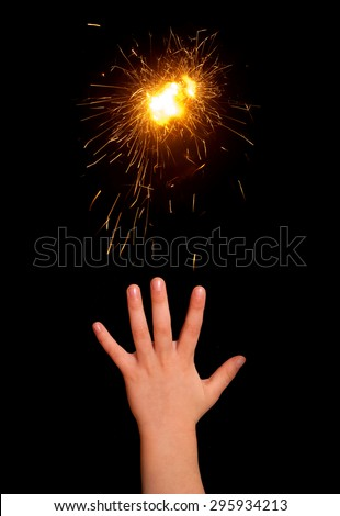 ?hildren hand with sparks on a black background - stock photo