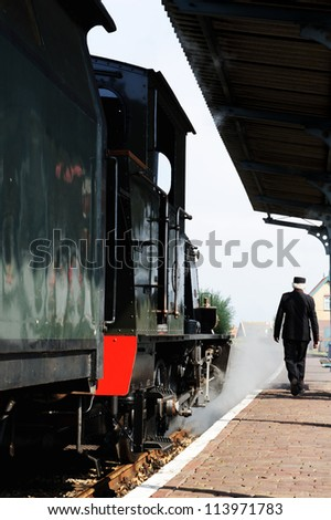 Historical steam train locomotive at station - stock photo