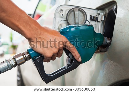 hold Fuel nozzle to add fuel in car at gas station - stock photo