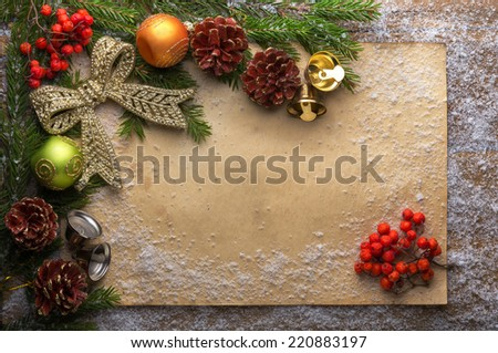 holiday decoration with paper, snow, bells, green branch and pine cones on wooden frozen table, christmas background  - stock photo