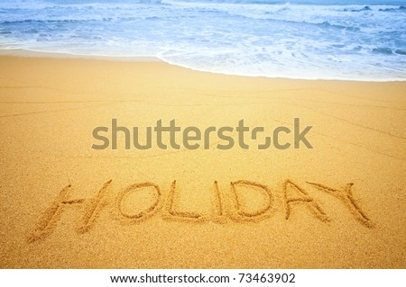 """""""Holiday"""" written in the sand on the beach blue waves in the background - stock photo"""