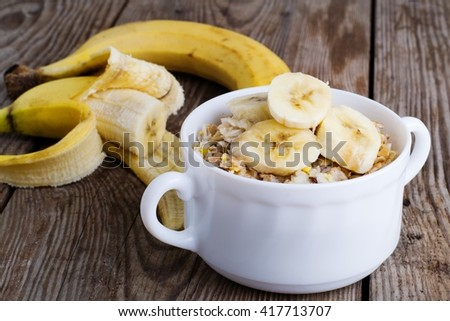 homemade oatmeal with a banana in a white plate for breakfast - stock photo