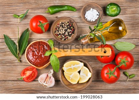 homemade tomato sauce in a wooden spoon on brown table and ingredients  - stock photo