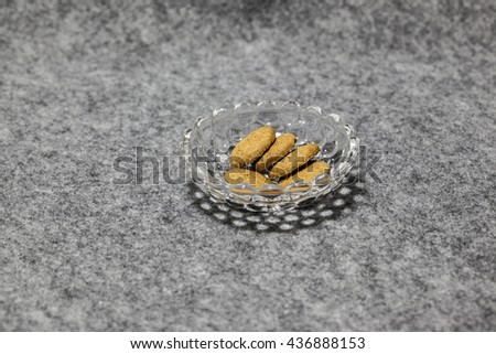 homemade whole meal cereal cookies made from whole wheat flour, vegetable oil, rice flour, corn flour,  rye flour and  fructo-oligosaccharides in a crystal bowl on a grey table cloth - stock photo