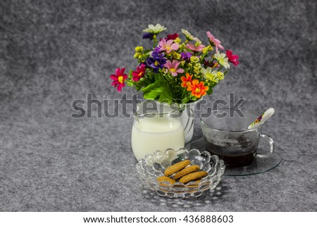 homemade whole meal cereal cookies made from whole wheat flour, vegetable oil, rice flour, corn flour in a crystal bowl with milk and coffee and a mimi flower pot  on a grey table cloth - stock photo