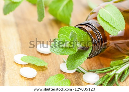 Homeopathic medication with tablets . Alternative medicine with herbal and homeopathic pills Bottle with tablets and herbal  on wooden table - stock photo