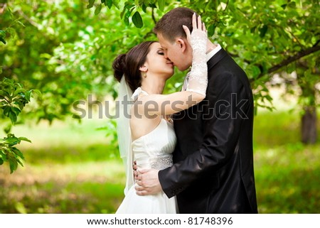 Horizontal portrait of young married couple kissing - stock photo