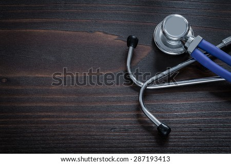 Horizontal view of stethoscope for medical check up on vintage wooden background medicine concept - stock photo