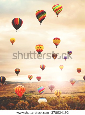 hot air balloons in the sky during sunrise toned with a retro vintage instagram filter app or action effect  - stock photo