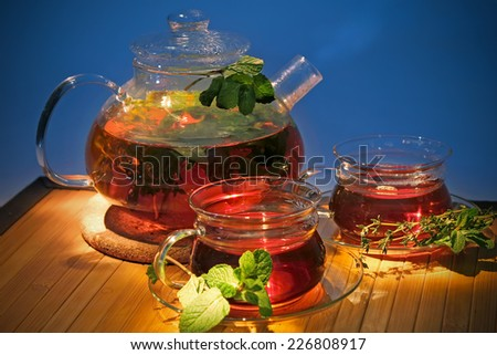 Hot tea with curative herbs in a glass teapot and cups on a wooden table on a cold blue background - stock photo