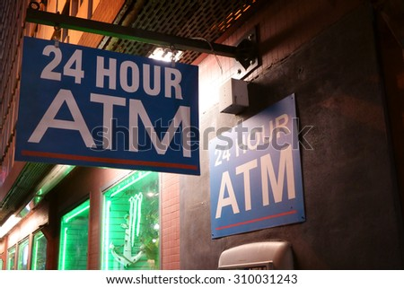 24 Hour ATM sign on side of store on a dark alley. - stock photo