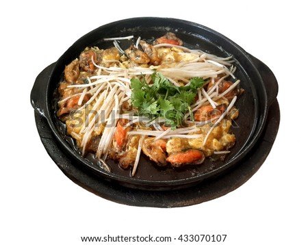 """""""Hoy tod"""" is a famous street food in Thailand. It consist of shellfishes such as oysters or mussels fried with other seafood, eggs and some vegetables and served in a hot plate.  - stock photo"""