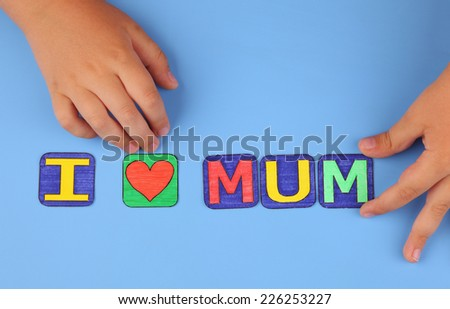 """I love mum"" spell out on blue background with child's hands. Letters drawn by me. - stock photo"